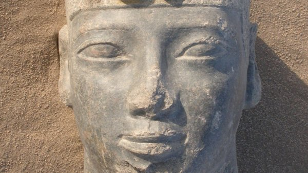 A close-up of the statue of Taharqa surrounded by sand.