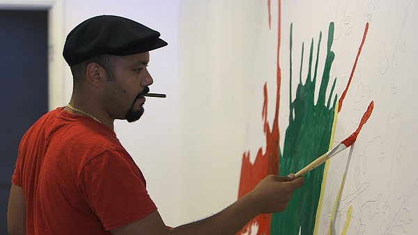Egyptian-born artist Michael Makram Nicola paints a mural...