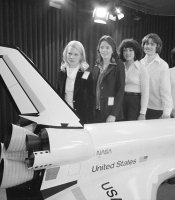 1978 class female astronauts pose in front of model shuttle.
