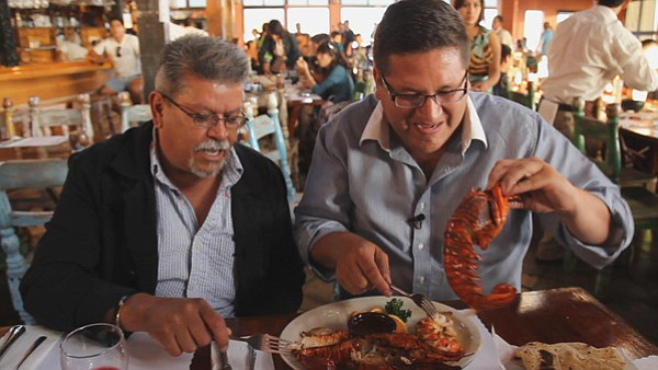 Host Jorge Meraz (right) has a feast of lobster at Puerto Nuevo.