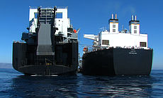The USNS Montford Point (right) maneuvers along...
