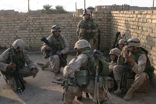 U.S. Marines huddle behind walls as they receive instruct...