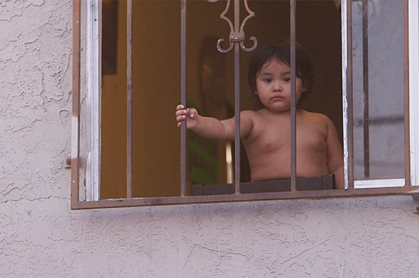 A child peers through a window facing a City Heights alle...