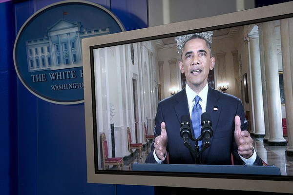 President Barack Obama is seen on a monitor in the briefi...
