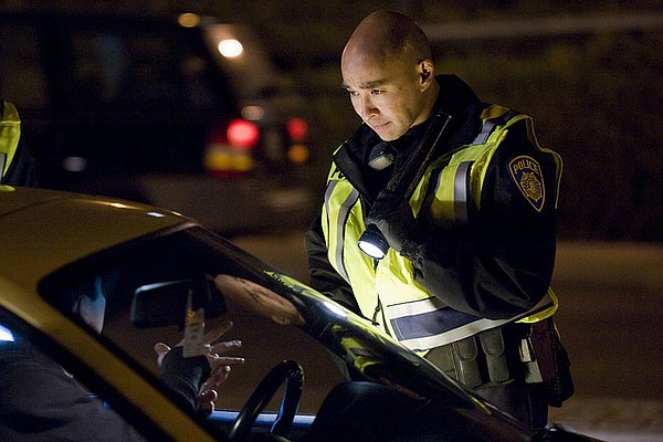 An officer inspects a California driver at a DUI checkpoi...