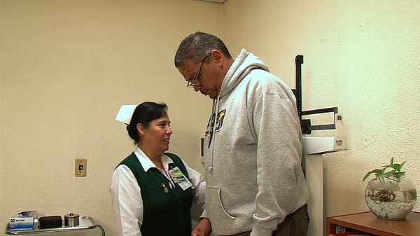 A nurse at Clinic No. 27 in Tijuana weighs Armando Huerta...