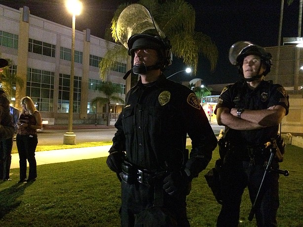 A San Diego Police officer in riot gear observes a protest Nov. 26, 2014 of a...