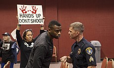 A San Diego police officer talks with protest l...