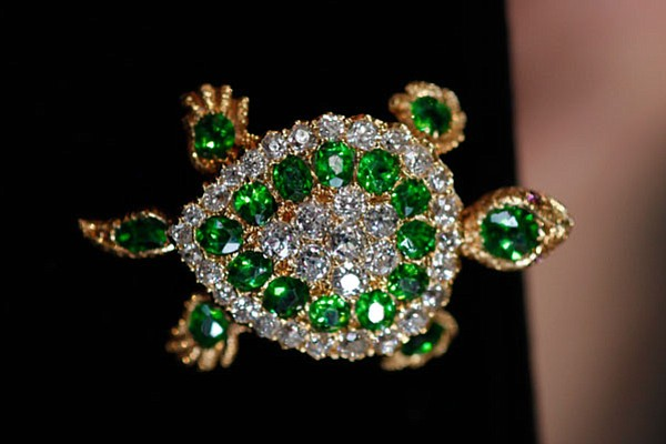 This demantoid, diamond, and ruby brooch, ca. 1890, was a...