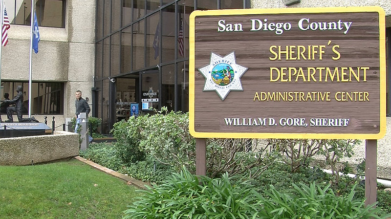 A man is shown walking out the front door of the San Diego County Sheriff's D...
