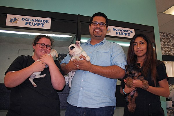 Oceanside Puppy owner David Salinas, center, and his empl...