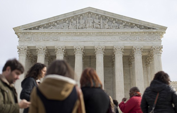 People wait outside to enter the U.S. Supreme Court in Wa...