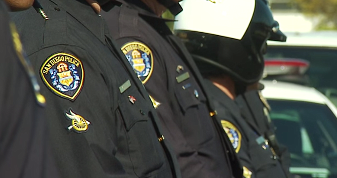 San Diego police officers stand in a line revealing a patch on the right shou...