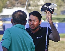 Jason Day, right, shakes hands with J.B. Holmes after winning a playoff against Holmes at the Farmers Insurance Open at the Torrey Pines Golf Course on the second extra hole with a par, Feb. 8, 2015.