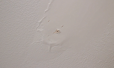 A hole is shown in Sherry Godat's ceiling Nov. 20, 2014. Godat says water streams from the hole whenever it rains.