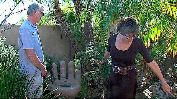 Bill and Camille Currier stand next to the backyard memorial to their son, Br...