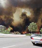 The Poinsettia fire, fueled by strong Santa Ana winds and extreme drought conditions, burns through a neighborhood in Carlsbad, May 2014.