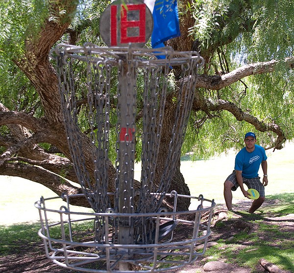 Angel Garcia, the Morley Field course pro, is pictured taking aim at a basket...