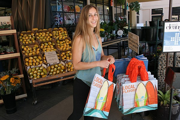 Carlsbad resident Haley Davern picks up a reusable bag to...