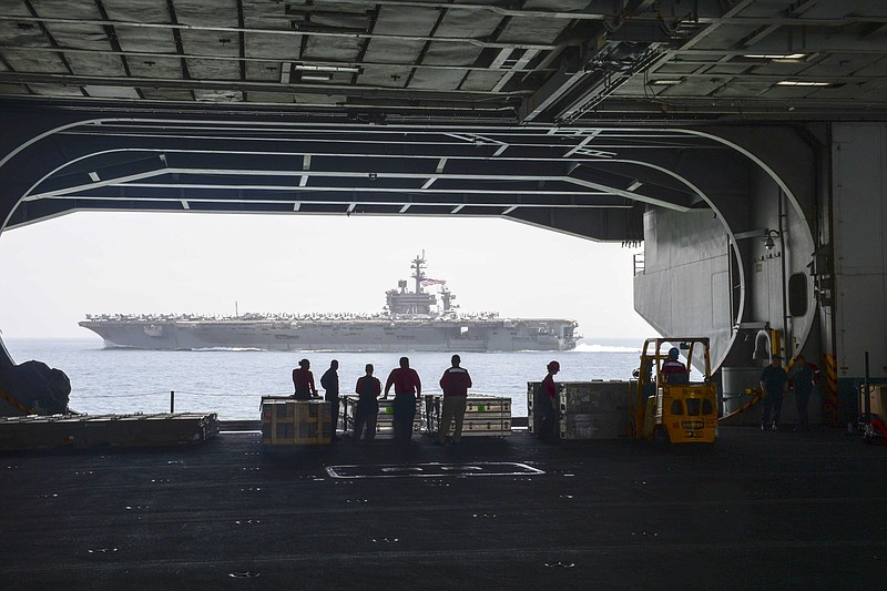 Sailors view the San Diego-based aircraft carrier USS Carl Vinson from the ha...