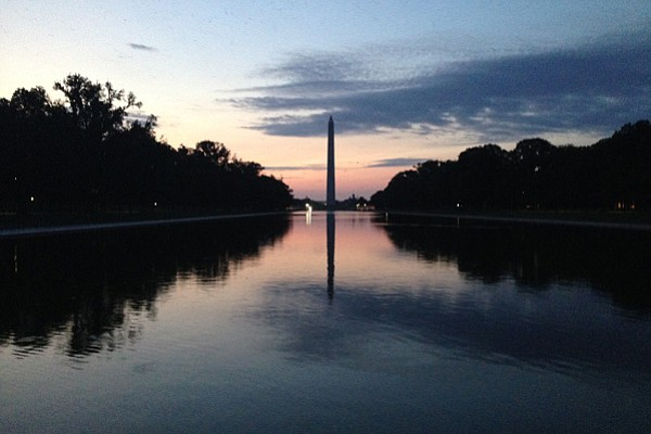 The sun rises over the Washington Monument and the reflec...