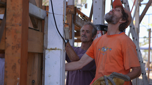 Volunteers help remove scaffolding from the Sn Salvador a...