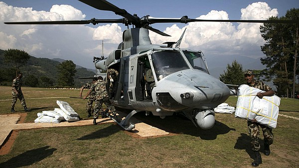 Nepalese military service members unload supplies from a ...