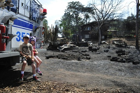 Children are pictured in front of a home that burned in H...