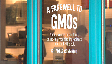 New signs at Chipotle advertise the burrito chain's decision to take GMOs off...