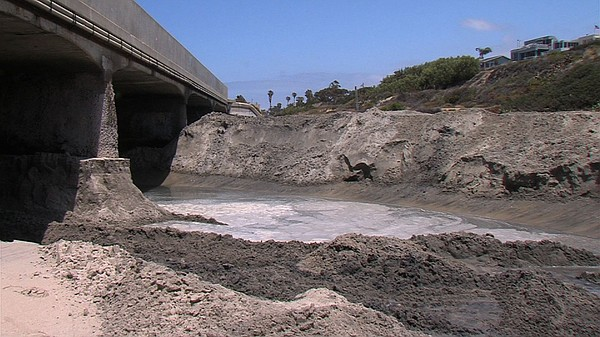 Sand clogs the pilings under the Highway 101 bridge which...