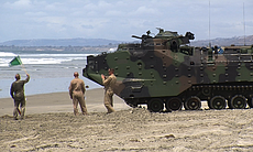 A Marine holds up a green flag to signal the dr...