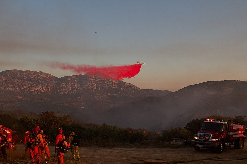 Firefighters on the ground watch as a plane drops retardant on the Wildcat fi...