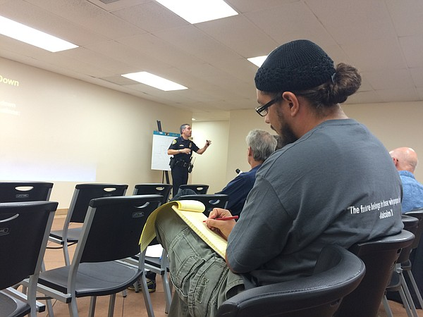 Paul Alexander takes notes during a San Diego Police Department presentation ...