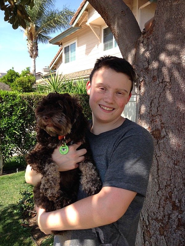 Sam Moehlig, 14, is seen holding his dog outside their Ra...