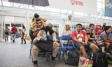 A man wearing a costume of stuffed puppy dogs c...