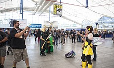 People in costume pose for photos at Comic-Con,...