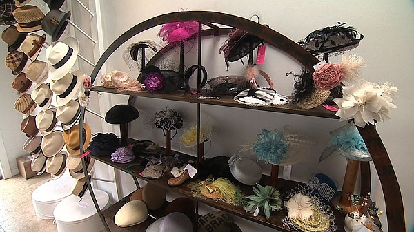 A rack of fascinators and pillbox hats sit in Jill Courte...