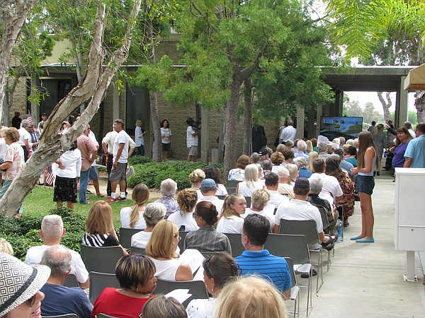An overflow crowd fills the courtyard outside Carlsbad Ci...