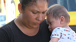 Leticia Barajas, a resident of Mineral de Santa Fe, stands near her home with her son, Aug. 27, 2015.