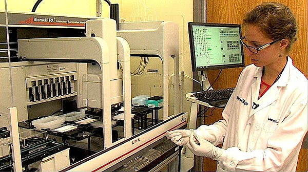 Post-doctor fellow Laura-Isabel McCall operates a drug discovery robot inside...