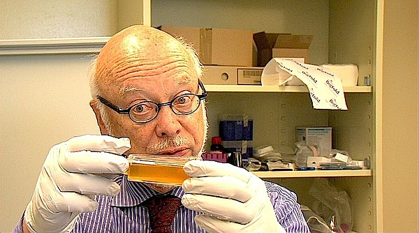 Dr. James McKerrow stands in the UCSD drug discovery lab holding a flask of l...