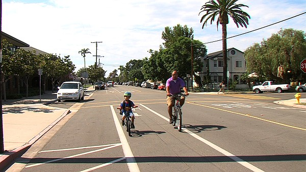 A father and son ride down a bike lane next to Coronado's...