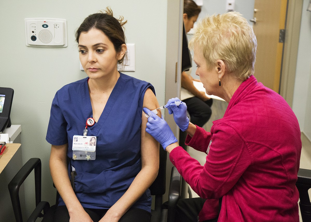 ​​Marcela Delatone, an environmental services worker at Palomar Health, ​​​​​​gets the influenza vaccination at Palomar Health.