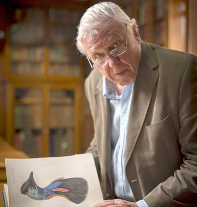 Sir David Attenborough with a book opened to a print of a...