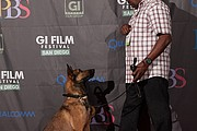 Jagger, the dog who plays Max in the film, poses with his handler on the GI Film Festival red carpet.