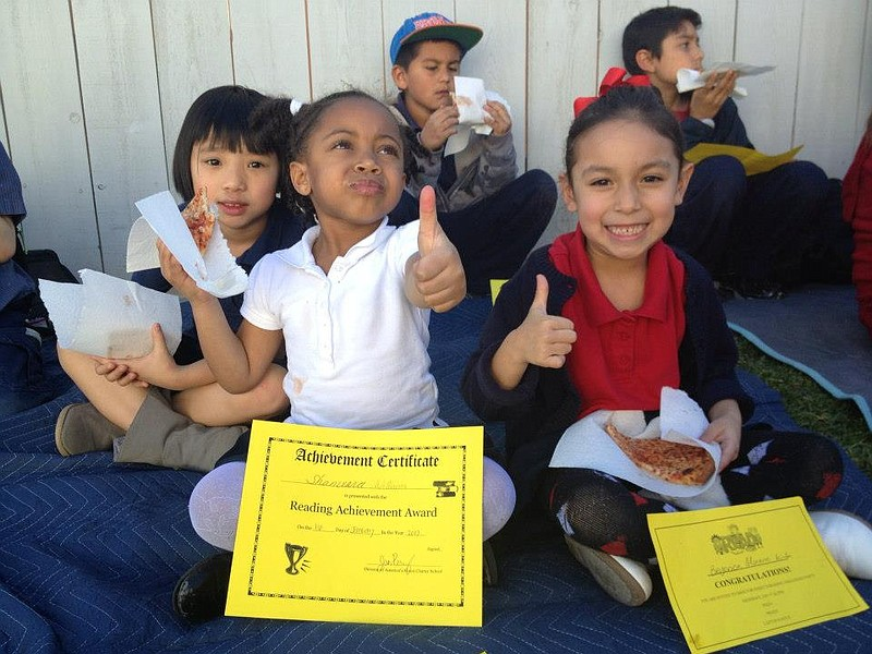 America's Finest Charter School students eat pizza at a 2013 party celebratin...
