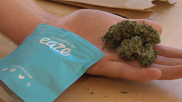 An eighth of an ounce of marijuana is seen next to the packaging of the pot d...
