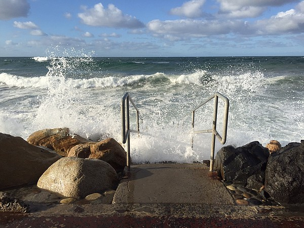 Waves crash against the stairs to the beach in Oceanside,...
