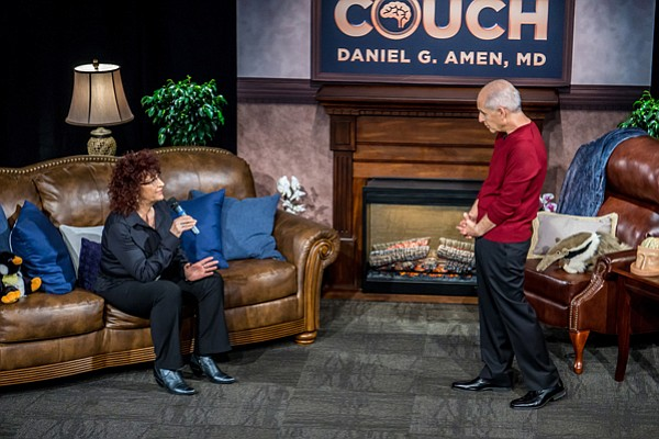 A guest interacts with Dr. Daniel Amen on the set of