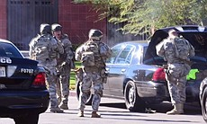 A SWAT team arrives at the scene of a shooting ...